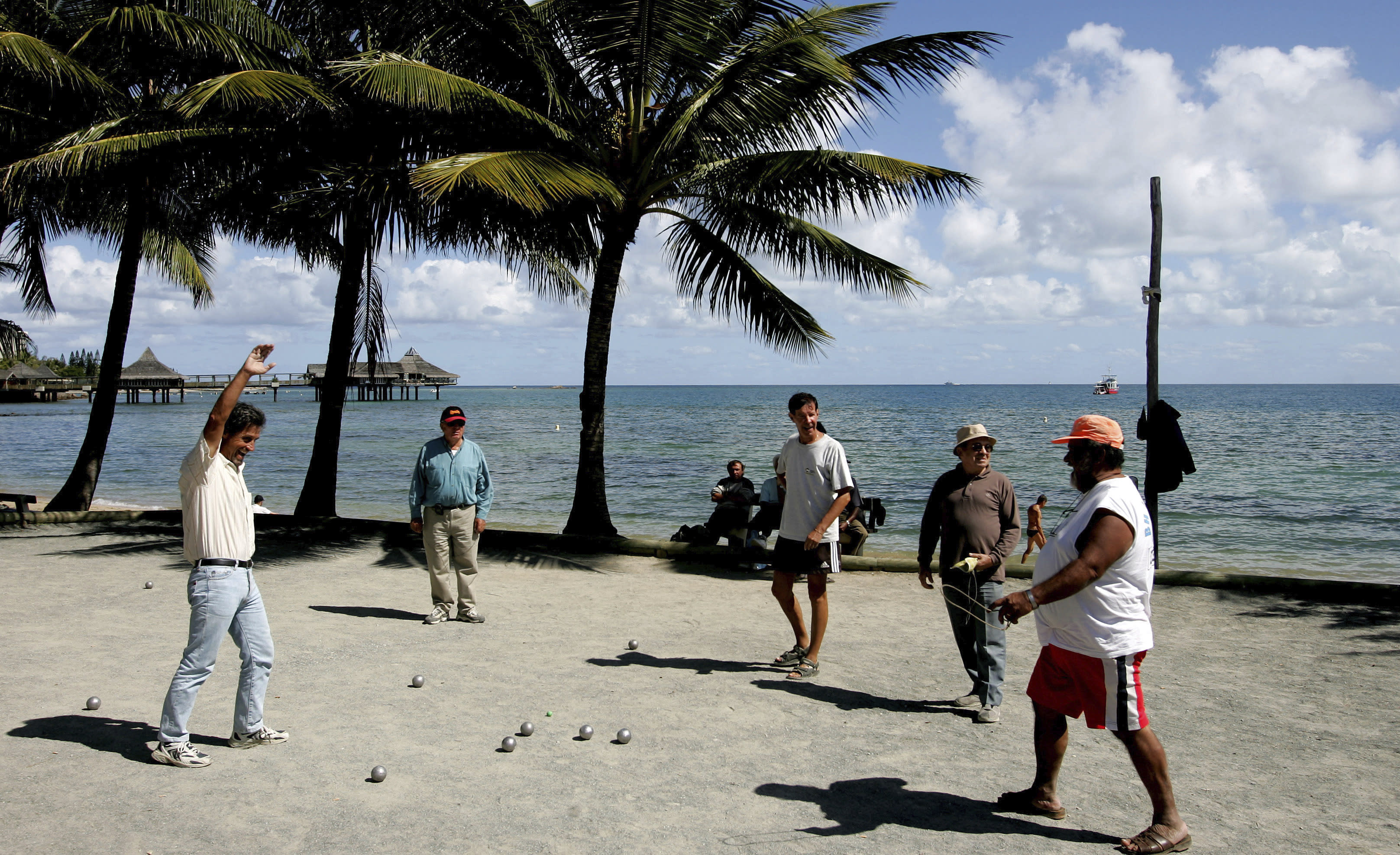 """FILE - In this Thursday, Sept. 22, 2005 file photo, locals on the beach in Noumea, New Caledonia, play the traditional ball game """"petanque"""". Voters in New Caledonia, a French archipelago in the South Pacific, are to choose whether they want independence from France in a referendum that marks a milestone in a three-decades-long decolonization effort. The vote on Sunday, Oct. 4, 2020 is key to determine the future of the archipelago east of Australia and its 270,000 inhabitants, including the native Kanaks, who once suffered from strict segregation policies, and the descendants of European colonizers. (AP Photo/Rob Griffith, file)"""