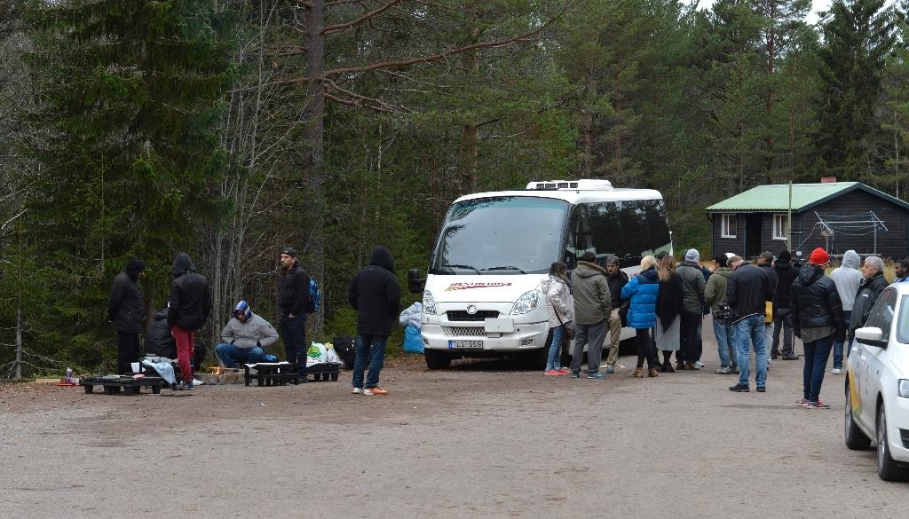 Migrants, and some journalists, sit and stand near a bus outside a temporary facility in the village of Limedsforsen in the Swedish province of Dalarna, on October 29, 2015 (AFP Photo/Nisse Schmidt)