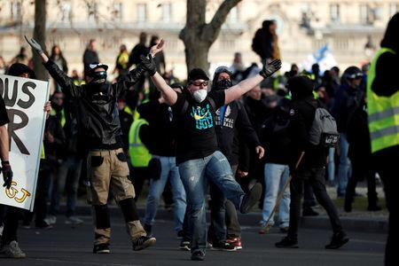 "FILE PHOTO: Protesters wearing yellow vests clash with French riot police near the Invalides during a demonstration by the ""yellow vests"" movement in Paris"