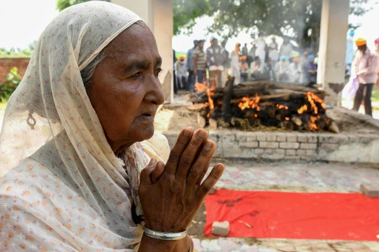 Veer Kaur, mother of a victim of toxic bootleg alcohol, stands next to her son's burning pyre in the village of Muchhal some 30 kilometres from Amritsar on August 1, 2020 (AFP Photo/NARINDER NANU)