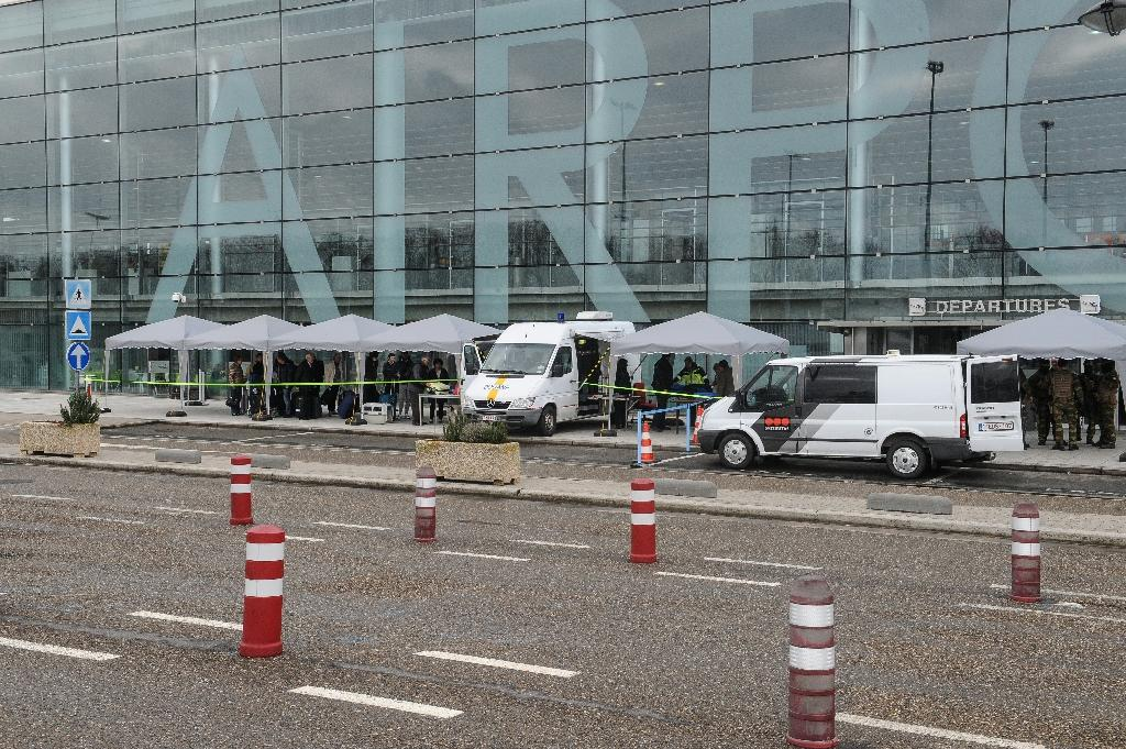 Passengers queue at a security check-point set outside Liege airport, on March 23, 2016, as extra security measures are being set one day after two massive suicide blasts by men with bombs in their bags hit the aiport