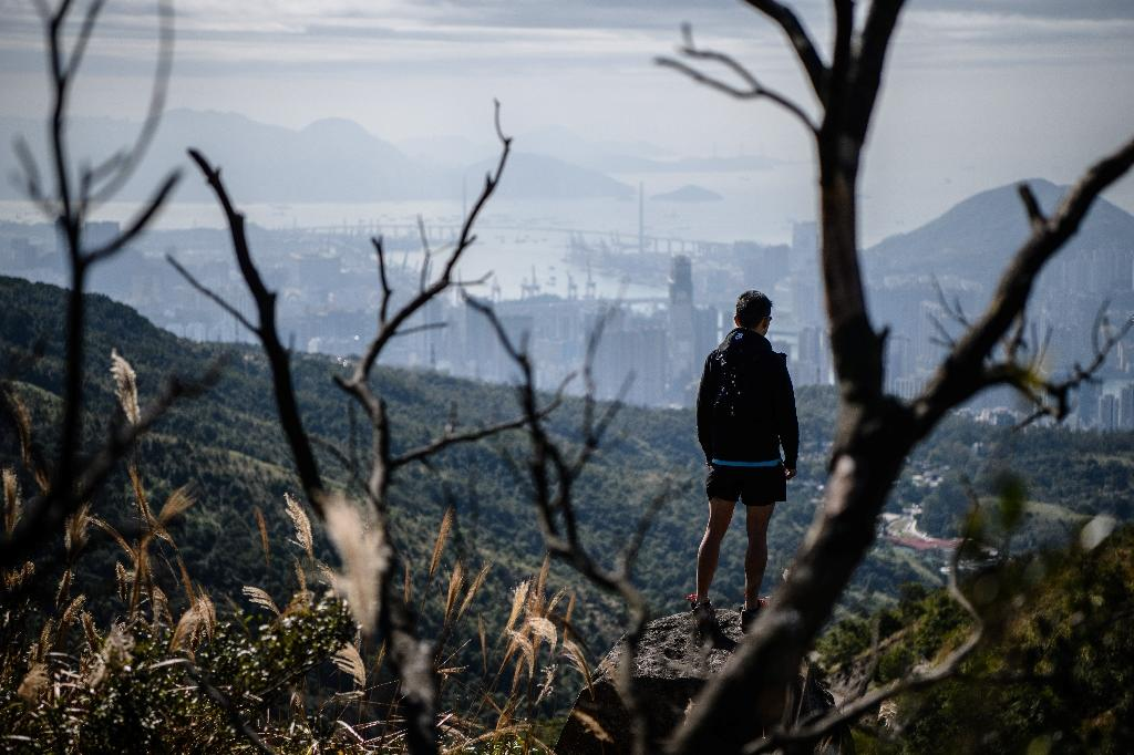 Within easy reach of Hong Kong's densely packed tower blocks and traffic, there is an extensive network of hiking trails which snake over hundreds of peaks across the territory and along its coastlines (AFP Photo/Anthony WALLACE)