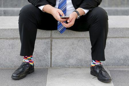 A businessman sits on a bench looking over his mobile phone in downtown San Francisco, California February 4, 2016. REUTERS/Mike Blake