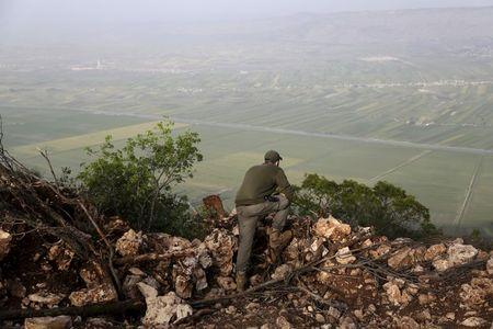 A rebel fighter stands on a hill overlooking al-Ghab plain, as he monitors the progress of the fighting from the Jabal al-Akrad area in Syria's northwestern Latakia province, April 29, 2015. REUTERS/Khalil Ashawi