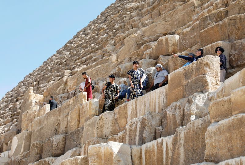Tourists climb the Great Pyramids of Giza, on the outskirts of Cairo
