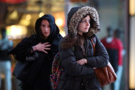 Women walk through the rain in Times Square in Manhattan in New York, U.S., March 7, 2018. REUTERS/Amr Alfiky