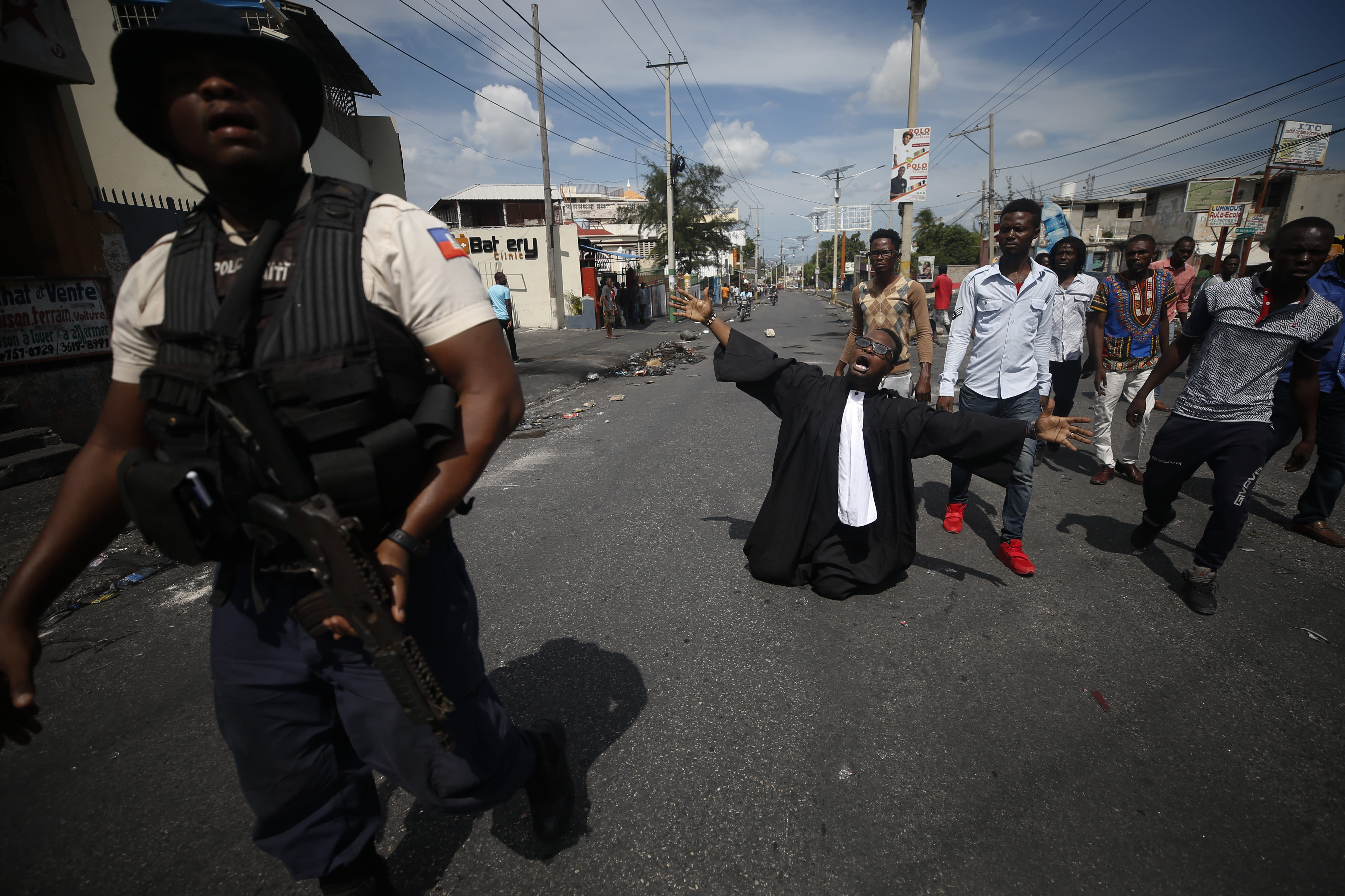 """Paseus Juvensky St. Fleur, who trained as a lawyer and is now an activist working for social justice, drops to his knees as protestors trying to set up a barricade across a major road argue with police trying to stop them, in Port-au-Prince, Haiti, Wednesday, Oct. 2, 2019. A group of men was protesting at the intersection after commissioning a mural of opposition organizer Jose Mano Victorieux, known as """"Badou,"""" who they said was executed Saturday night by unknown assailants.(AP Photo/Rebecca Blackwell)"""