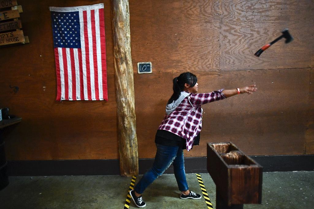 On a busy Friday night at Stumpy's Hatchet House in New Jersey, it sounds like this: the thud of the blade sticking into a wooden target, people cheering a good toss, and a bell ringing out when somebody scores a bull's eye (AFP Photo/Jewel SAMAD)