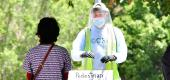 A volunteer dressed in full protective gear gives directions to a woman at a walk-in COVID-19 test site on June 30, 2020 in Los Angeles. (FREDERIC J. BROWN/AFP via Getty Images)