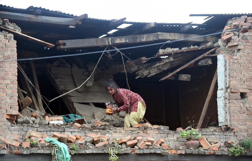 A girl looks for belongings in her damaged house in Bhaktapur on the outskirts of Kathmandu (AFP Photo/Prakash Singh)