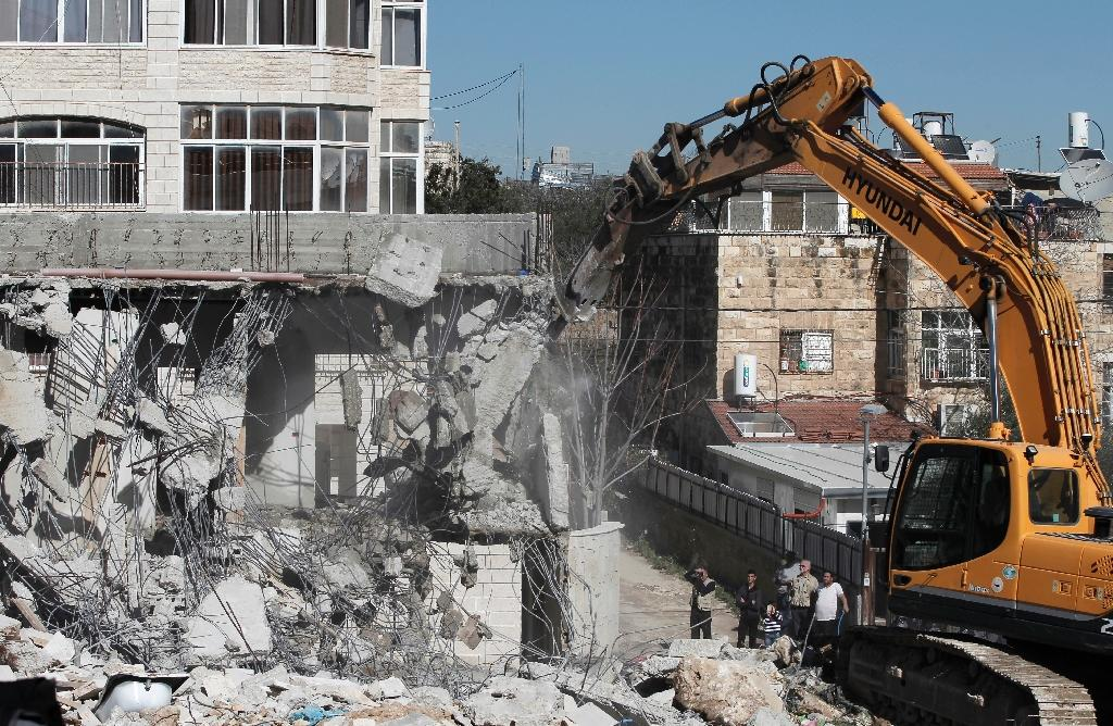 A bulldozer hired by the Jerusalem municipality destroys a Palestinian house in annexed East Jerusalem on the grounds that it was built without a construction permit (AFP Photo/Ahmad Gharabli)