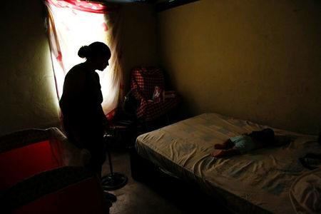 Yelis Toussaint looks to her son Jhonanyel, while he sleeps on a bed, before her sterilization surgery at their home in Charallave, Venezuela July 7, 2016. REUTERS/Carlos Garcia Rawlins