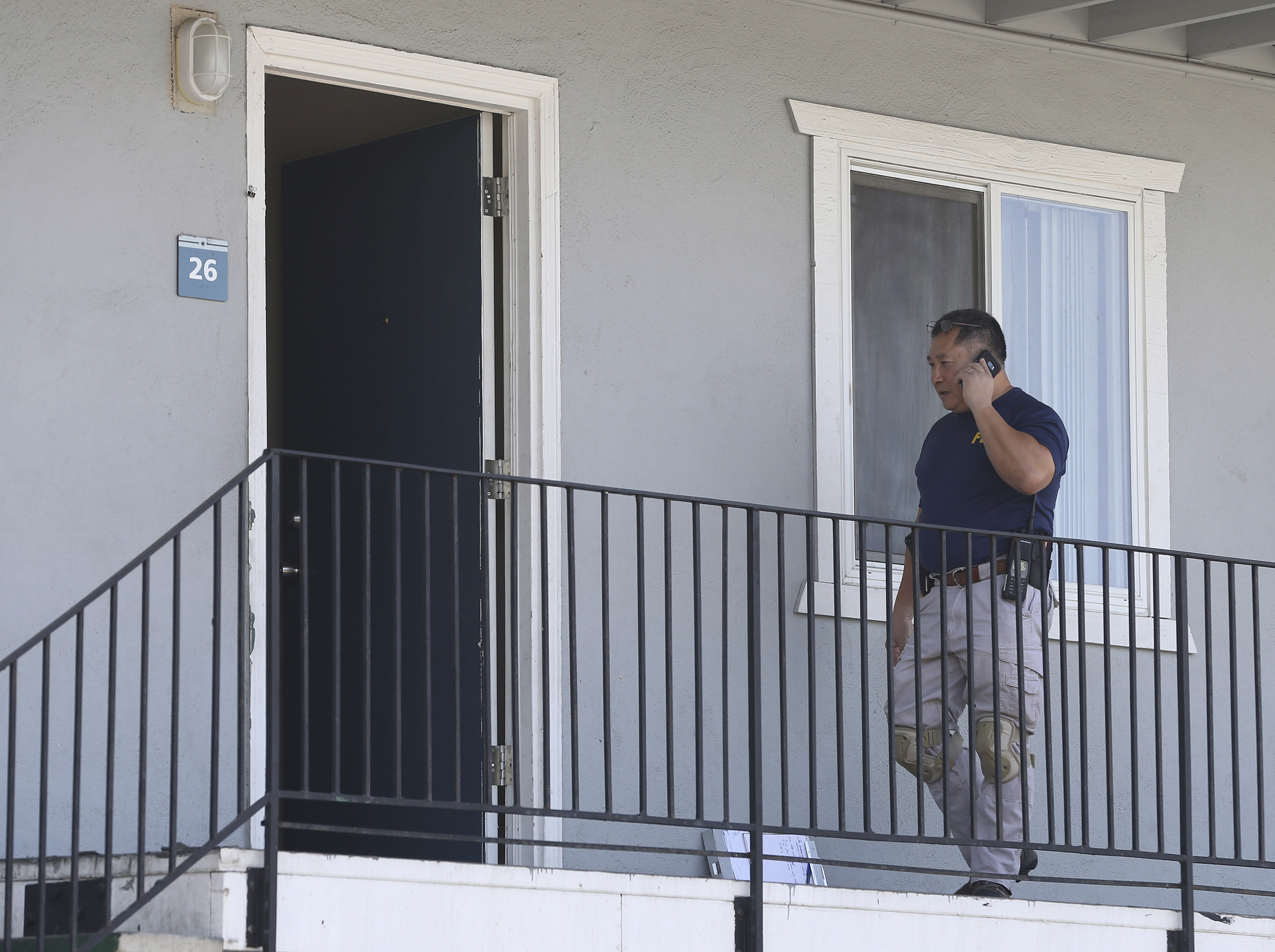 A federal agent makes a call outside the apartment following the arrest of a 45-year-old Iraqi refugee, Omar Ameen, Wednesday, Aug. 15, 2018, in Sacramento, Calif. Ameen was arrested on a warrant alleging that he killed an Iraqi policeman in 2014 while serving with the Islamic State terror organization. (AP Photo/Rich Pedroncelli)