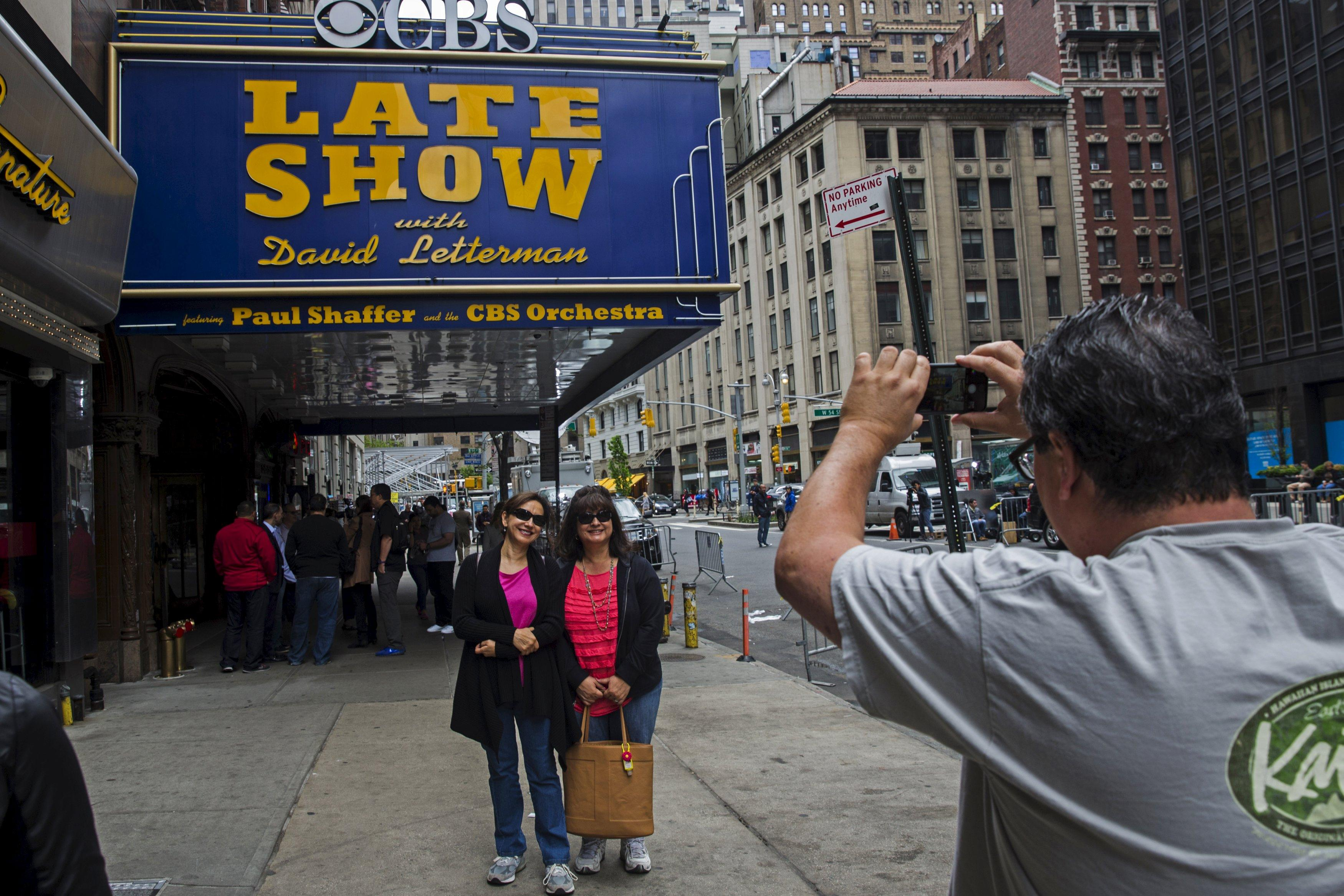 """A fan stops to take a photograph of the outside of Ed Sullivan Theater in Manhattan as David Letterman prepares for the taping of tonight's final edition of """"The Late Show"""" in New York May 20, 2015. REUTERS/Lucas Jackson"""