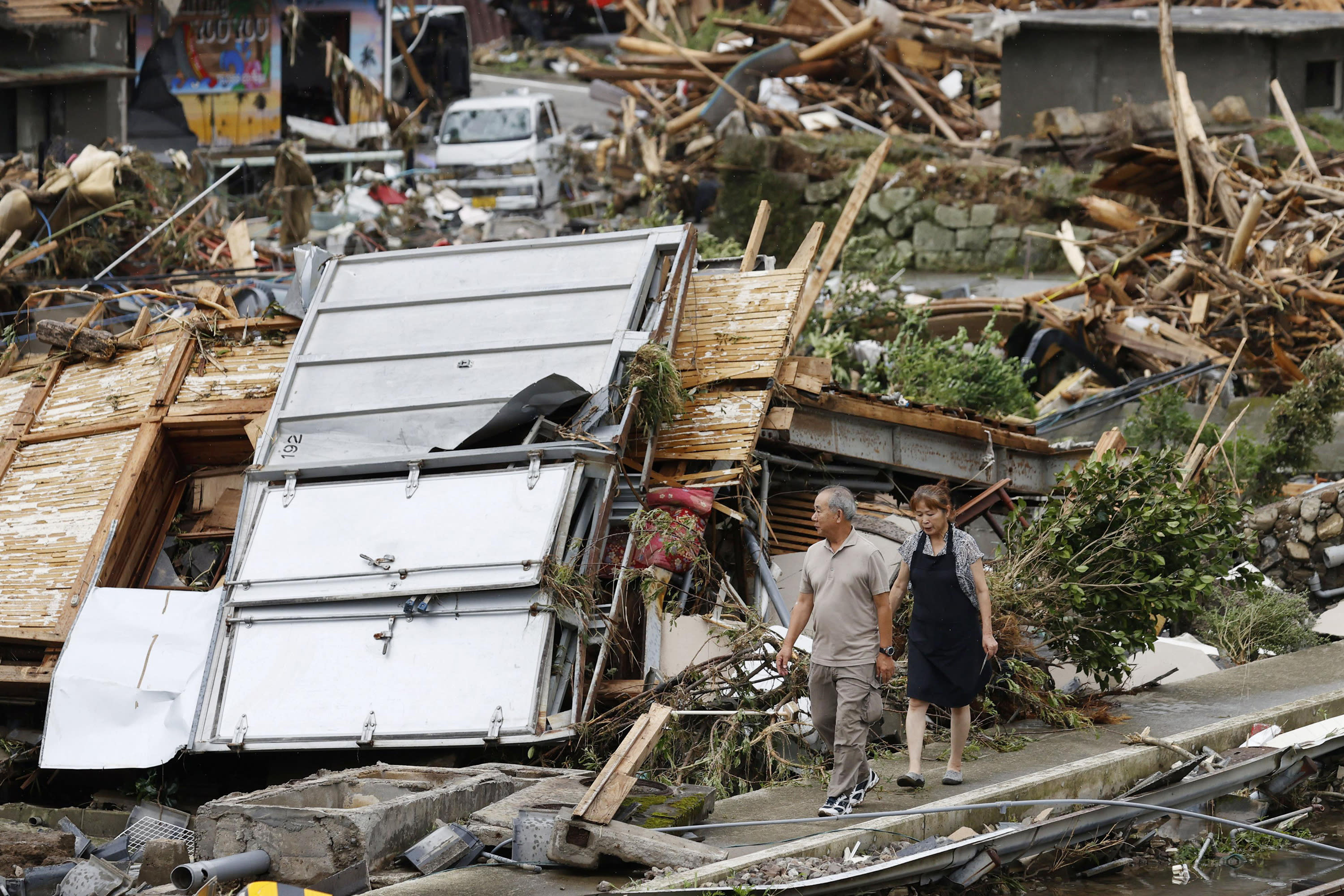 A couple walks near debris from a heavy rain in Kumamura, Kumamoto prefecture, southern Japan Monday, July 6, 2020. Rescue operations continued and rain threatened wider areas of the main island of Kyushu. (Kyodo News via AP)