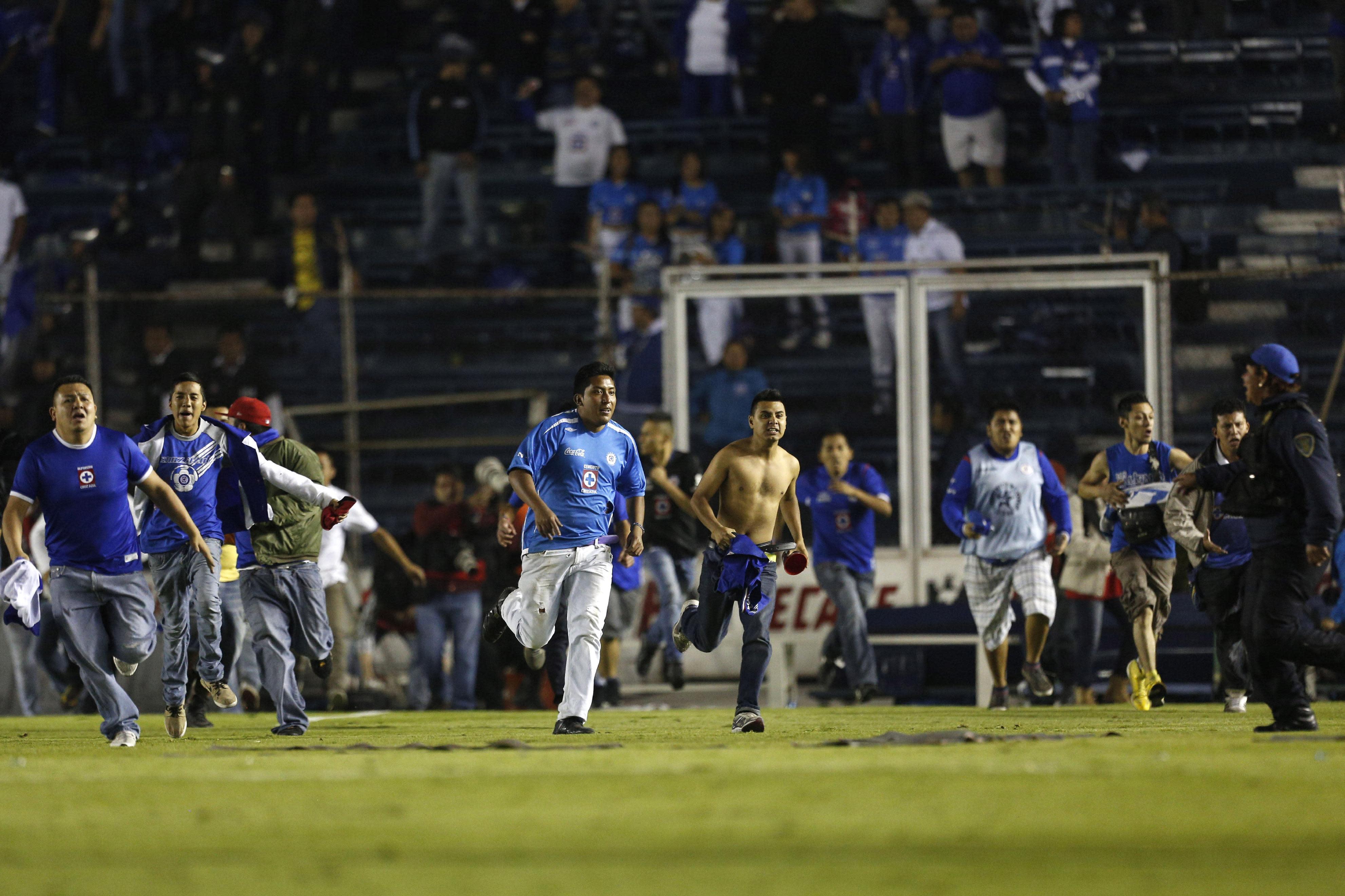 Un grupo de aficionados del Cruz Azul invade la cancha al final del encuentro en que su equipo fue eliminado por el Toluca en los cuartos de final del Apertura mexicano, el sábado 30 de noviembre de 2013 (AP Photo/Moisés Castillo)