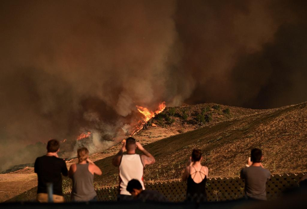 """Local residents watch a blaze dubbed the """"Sand Fire"""" as it moves towards Fair Oaks Canyon housing estate in Santa Clarita, California on July 24, 2016 (AFP Photo/Mark Ralston)"""