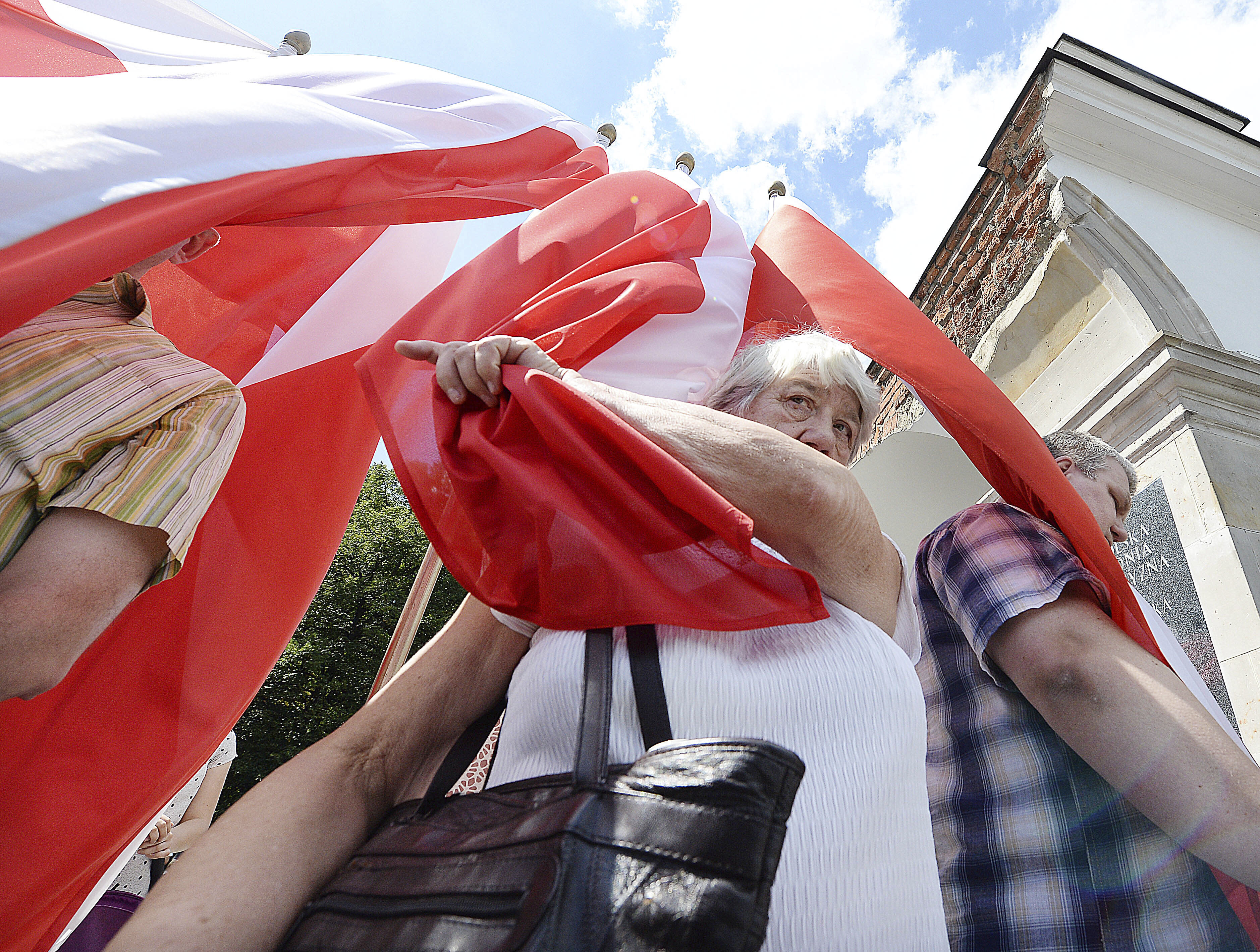 People hold Polish national flags as they attend an event by Polish officials and war veterans to pay tribute to a World War II-era underground force that collaborated with Nazi German forces toward the end of the war in their battle against the Communists, in Warsaw, Poland, Sunday, Aug. 11, 2019. President Andrzej Duda's official patronage and the presence of ruling party officials underlined the right-wing government's rehabilitation of a partisan unit that fought both Germans and Soviets and which is celebrated by the far right. (AP Photo/Czarek Sokolowski)