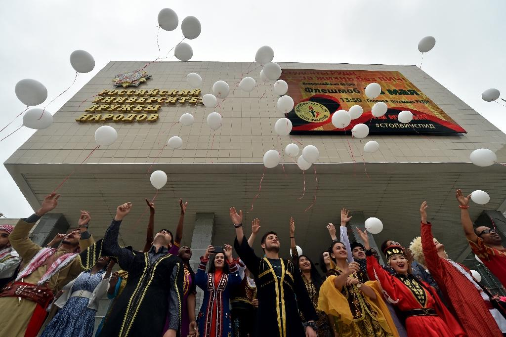 Foreign students of the University of Peoples' Friendship wearing national costumes release white balloons during a HIV/AIDS awareness rally in front of the university's main building in Moscow, in May 2016