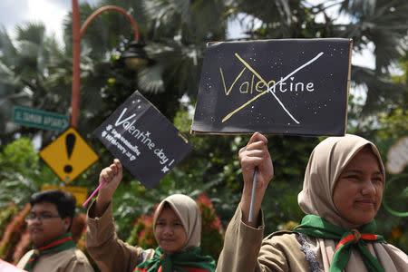 Muslim students hold posters during a protest against Valentine's Day celebrations in Surabaya, Indonesia, February 13, 2017 in this photo taken by Antara Foto. Antara Foto/Zabur Karuru/ via REUTERS