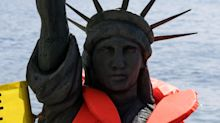 The Latest: Statue of Liberty in a lifejacket at G-7 protest