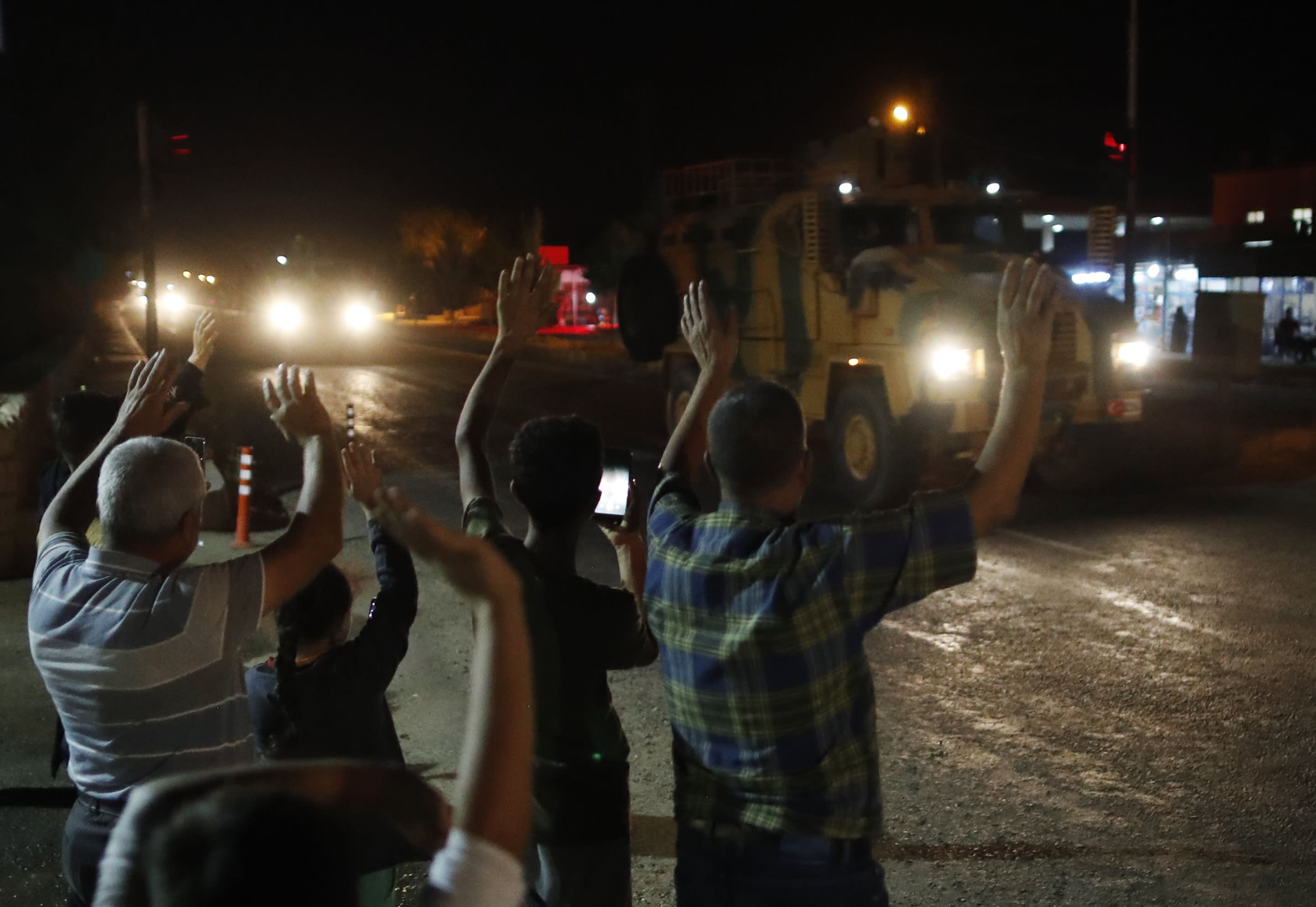 Local residents jeer and applaud as a convoy of Turkish forces vehicles and trucks carrying tanks and armoured personnel carriers driven in Sanliurfa province southeastern Turkey Tuesday Oct. 8 2019. The Turkey- Syria border has became a hot spot