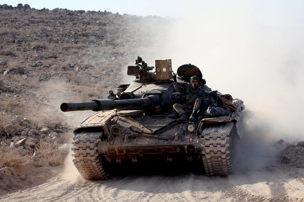 Syrian forces drive a tank on a road during a military operation against the Islamic State (IS) group in the villages of Zarour and Khanaser, in the Aleppo governorate, on February 26, 2016 (AFP Photo/Georges Ourfalian)