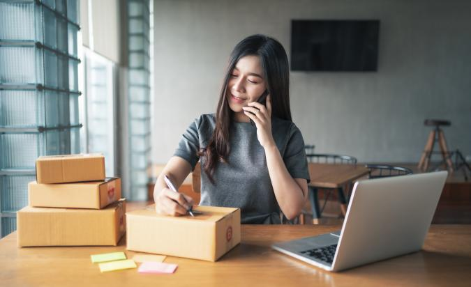 Young business woman working selling online. Entrepreneur owner using smartphone or laptop taking receive and checking online purchase shopping order to preparing pack product box. Packing goods for delivery to customer. Online selling. E-commerce. Online Shopping