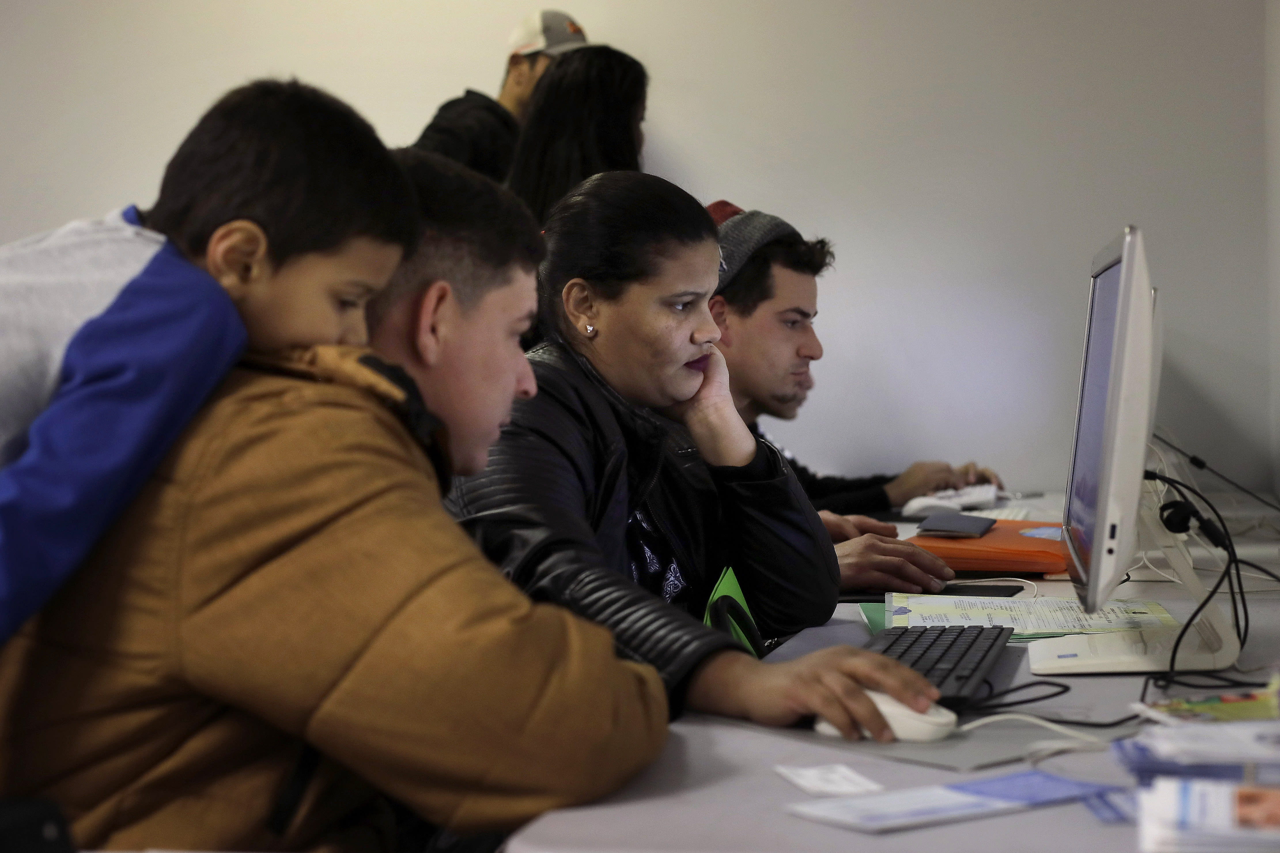 In this Wednesday, Dec. 4, 2019 photo Helison Alvarenga, of Brazil, second from left, sits with his 6-year-old son, David, left, and 24-year-old wife, Amanda, center, as they use a computer monitor while pursuing replacement passports at the New England Community Center, in Stoughton, Mass. Alvarenga, a 26-year-old from the Brazilian state of Minas Gerais, arrived in Massachusetts about four months ago after crossing the Mexican border at Juarez with his family. The three were at the community center Dec. 4, to apply for new Brazilian passports, which Alvarenga says were seized by border officials. (AP Photo/Steven Senne)