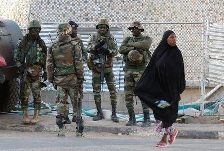 A woman passes near members of the regional ECOWAS, in Banjul