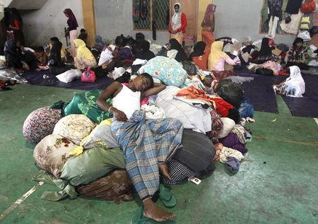 A migrant, believed to be Rohingya, sleeps on a pile of donated clothes inside a shelter where he is staying in since being rescued along with hundreds of others on Sunday from boats in Lhoksukon, Indonesia's Aceh Province May 12, 2015. REUTERS/Roni Bintang