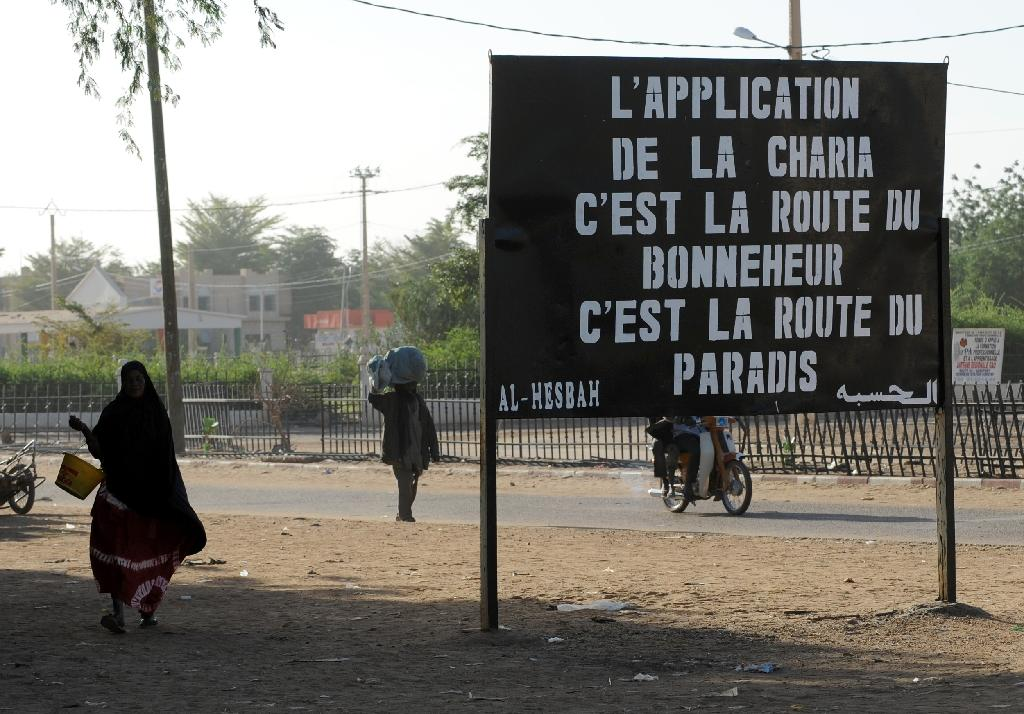 """Malians walk past a billboard left by the MUJAO, an offshoot of Al Qaeda in the Islamic Maghreb, on January 30, 2013, reading """"Enforcing Sharia is the road to happiness, it is the road to paradise,"""" in the northern city of Gao"""