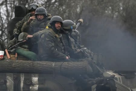 Members of the Ukrainian armed forces ride on an armoured personnel carrier near Artemivsk, eastern Ukraine, March 2, 2015. REUTERS/Gleb Garanich