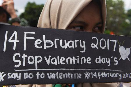 A Muslim student holds a poster during a protest against Valentine's Day celebrations in Surabaya, Indonesia, February 13, 2017 in this photo taken by Antara Foto. Antara Foto/Zabur Karuru/ via REUTERS