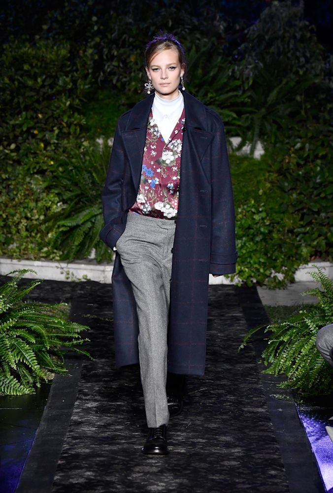 Model wears a menswear-style PJ shirt, gray trousers, and navy coat from the Erdem x H&M collection. (Photo: Getty