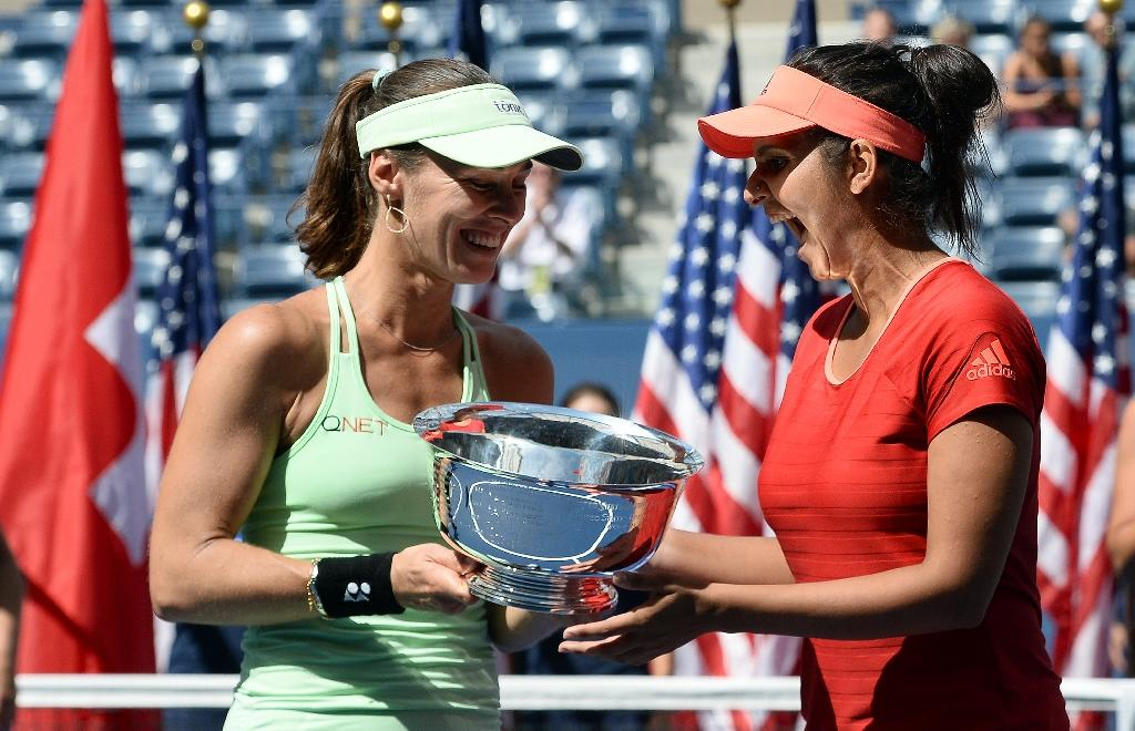 Sania Mirza (R) of India and Martina Hingis of Switzerland celebrate with their trophy after defeating Casey Dellacqua of Australia and Yaroslava Shvedova of Kazakhstan in the US Open women's double final in New York on September 13, 2015 (AFP Photo/Jewel Samad)