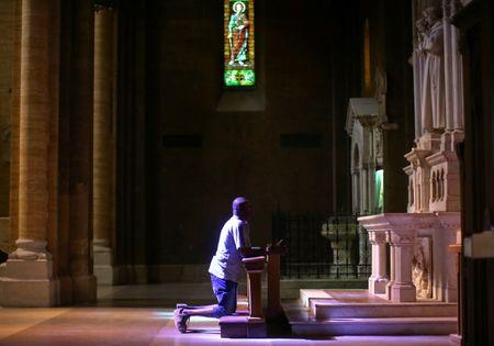 Nigerian Charles Otokiti, 37, who was rescued at sea after passing through Libya in 2016, prays in a church in Rome, Italy, July 5, 2018. Picture taken July 5, 2018. REUTERS/Alessandro Bianchi