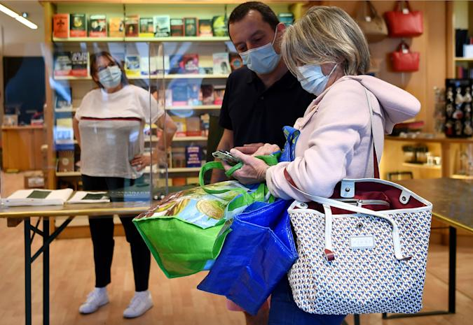 """A books seller wearing a face mask looks at a customer's smartphone at a bookstore in Neuilly-sur-Seine, on April 28, 2020, on the 43rd day of a lockdown in France aimed at curbing the spread of the COVID-19 disease, caused by the novel coronavirus. - Bookshops are among the hardest hit by the lockdown measures put in place since March 17. Until stores reopen on May 11, many establishments have already set up a """"click & collect"""" service to provide customers with a book they have ordered. (Photo by FRANCK FIFE / AFP) (Photo by FRANCK FIFE/AFP via Getty Images)"""
