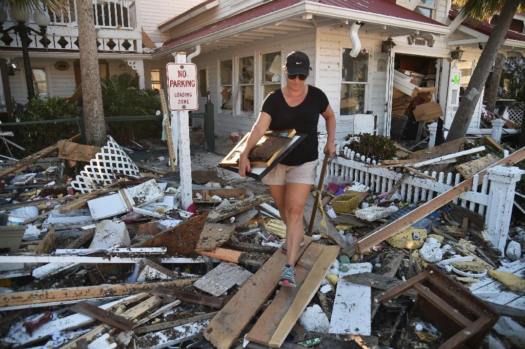 Brandy Jessen helps recovering belongings from her mother's house damaged by Hurricane Michael, in Mexico Beach, Florida, on October 13, 2018, three days after Hurricane Michael hit the area (AFP Photo/HECTOR RETAMAL)