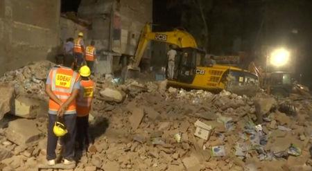 Workers watch as an excavator clears the debris at the site after a four-story hotel collapsed in a crowded part of the central Indian city of Indore late on Saturday, in this still image taken from video released on April 1, 2018. ANI/via REUTERS TV
