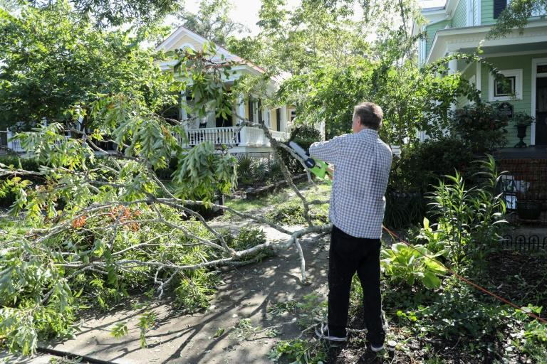 Residents of Wilmington clean up tree branch debris after Hurricane Isaias made landfall near the town in North Carolina (AFP Photo/Logan Cyrus)