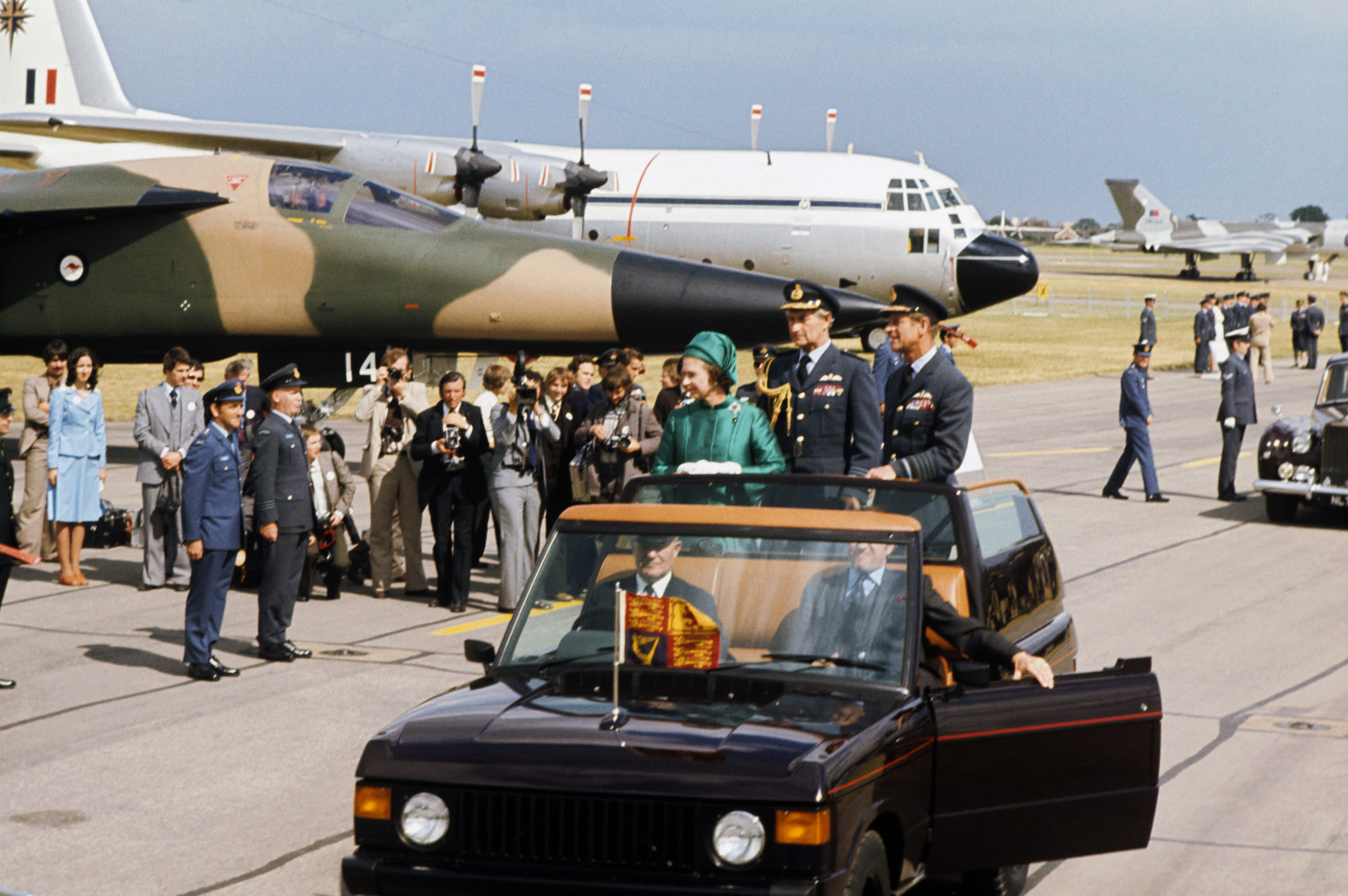 Queen Elizabeth II and the Duke of Edinburgh (in uniform as a Marshal of the RAF) driving in an open field car along the lines of aircraft and crews at the Royal Review of the Royal Air Force, at RAF Finningley, during her Silver Jubilee tour of Great Britain