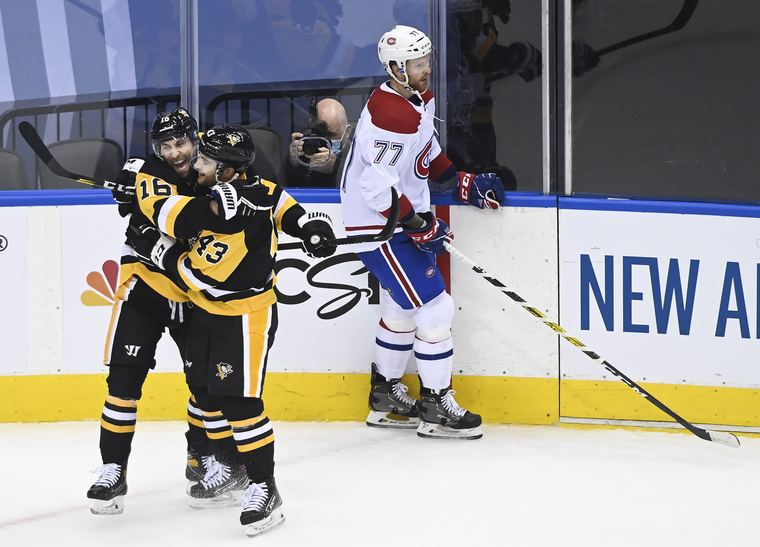 Pittsburgh Penguins left wing Jason Zucker (16) celebrates his goal with teammate Conor Sheary (43) as Montreal Canadiens defenseman Brett Kulak (77) skate by during the third period of an NHL hockey playoff game Monday, Aug. 3, 2020 in Toronto. (Nathan Denette/The Canadian Press via AP)