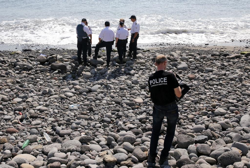 Police officers inspect debris found on a beach in Saint-Denis on Reunion Island in the Indian Ocean on August 2, 2015 (AFP Photo/Richard Bouhet)
