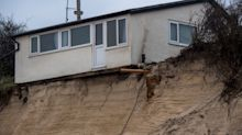 Clifftop homes begin to crumble into the sea in Norfolk as Britain is battered with harsh winds