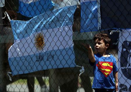 "A boy stands next to an Argentine national flag with a message in support of the 44 crew members of the missing at sea ARA San Juan submarine outside an Argentine naval base in Mar del Plata, Argentina November 25, 2017. Words on the flag read ""ARA San Juan, we wait for you"". REUTERS/Marcos Brindicci"