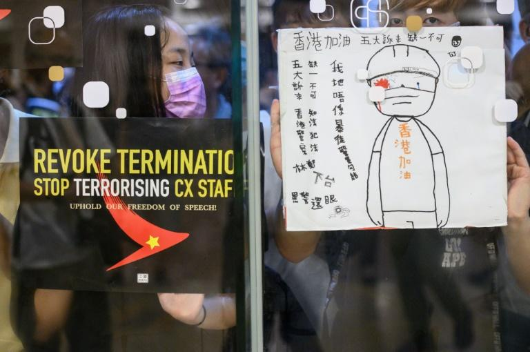 Protesters stuck posters outside a shopping mall in an August rally to support Cathay Pacific staff in Hong Kong (AFP Photo/Philip FONG)