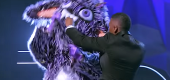 Host Nick Cannon tries to stop the Gremlin from ripping off his own costume. (Photo: Fox)