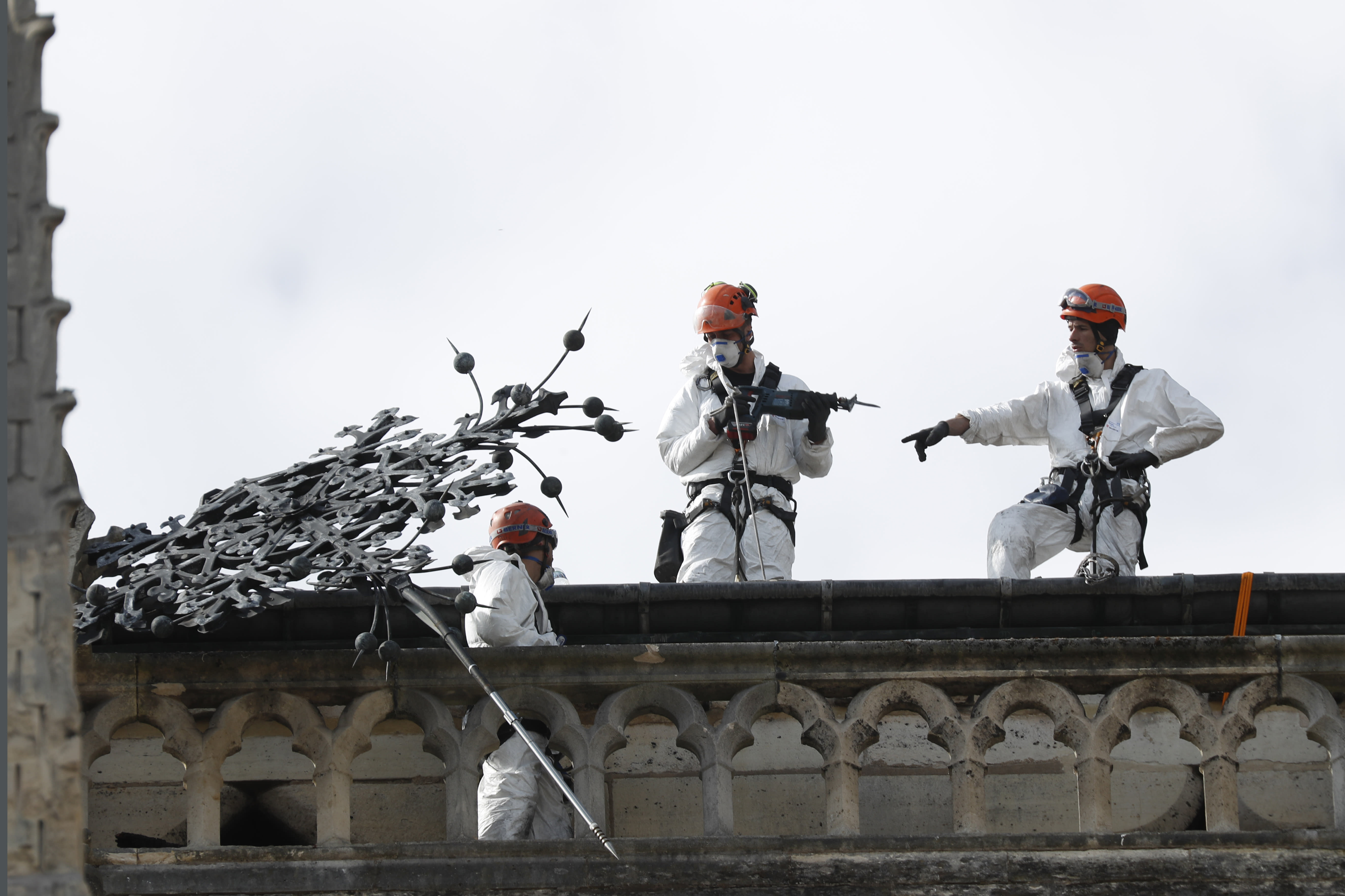Workers stand on a roof of Notre Dame cathedral Wednesday, April 24, 2019 in Paris. Professional mountain climbers were hired to install synthetic, waterproof tarps over the gutted, exposed exterior of Notre Dame Cathedral, as authorities raced to prevent further damage ahead of storms that are rolling in toward Paris. (AP Photo/Thibault Camus)
