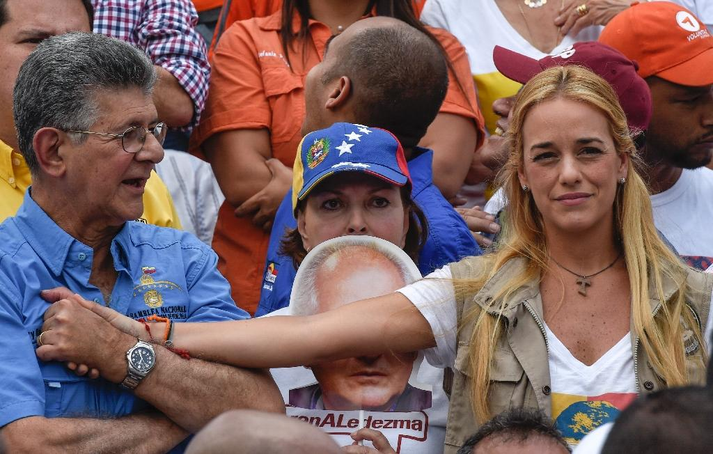 Lilian Tintori (R), wife of Venezuelan jailed opposition leader Leopoldo Lopez, holds hands with the president of the Venezuelan National Assembly, Henry Ramos Allup (L), during a rally in Caracas on July 9, 2016 (AFP Photo/Juan Barreto)